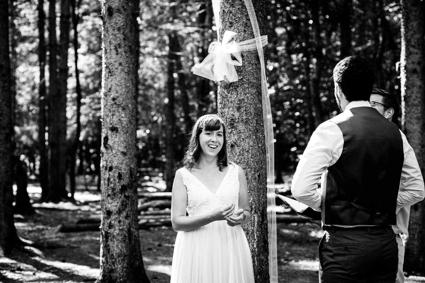 beautiful bride laughs during her intimate forested wedding ceremony
