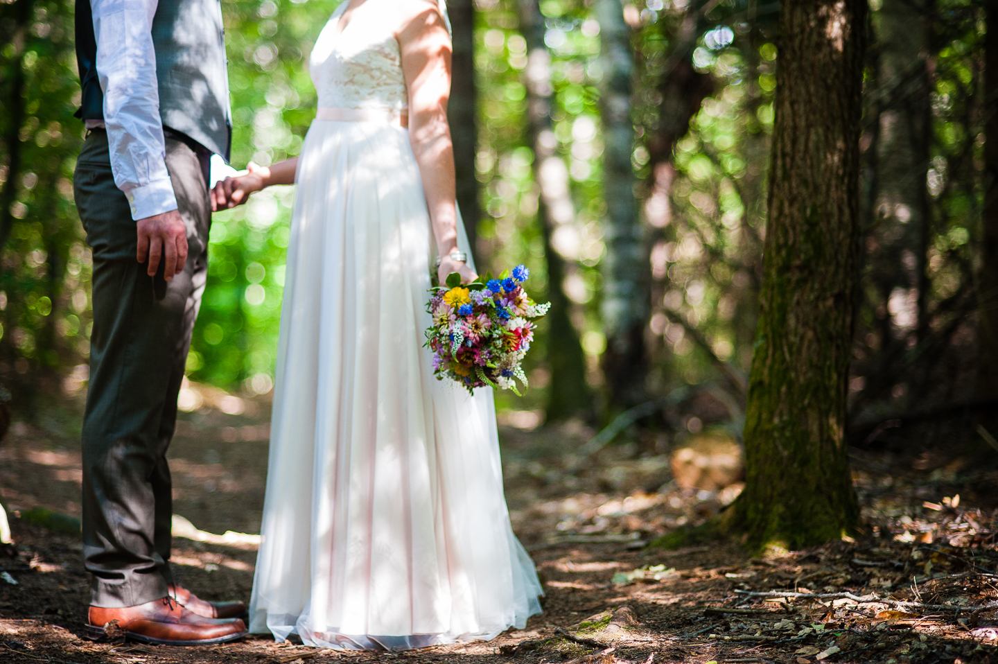 bride and groom hold hands in the middle of the woods