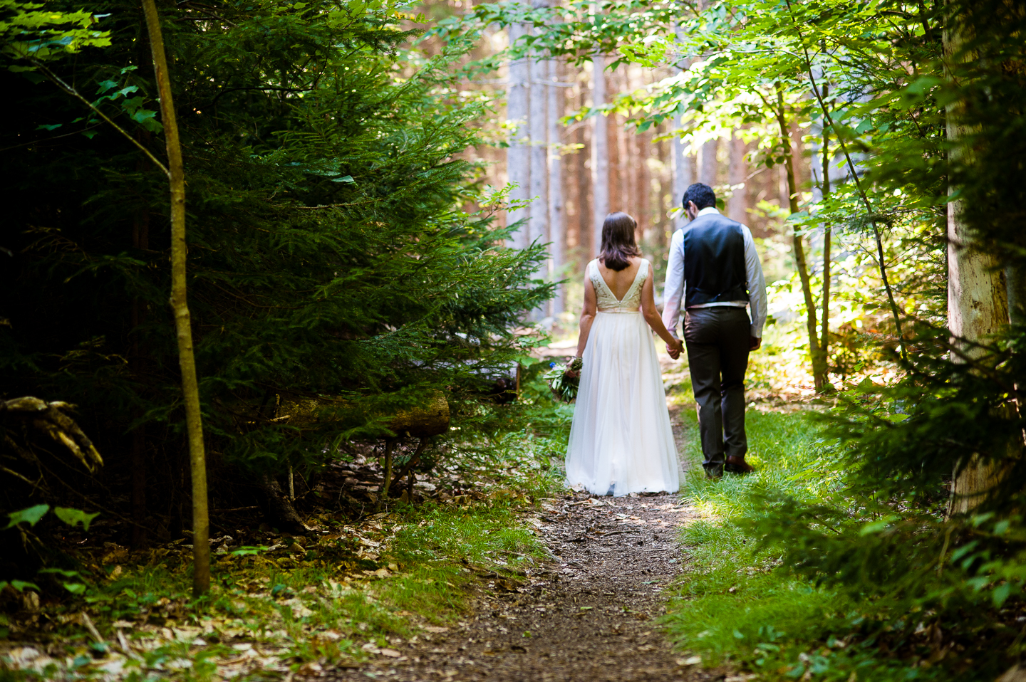 bride and groom hold hands and walk down beautiful wooded path