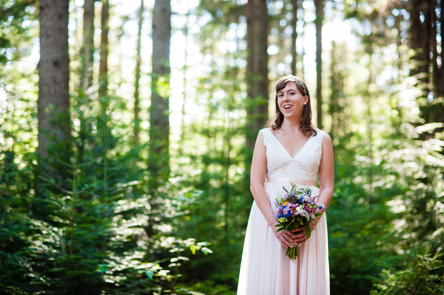 Gorgeous bride poses for a bridal portrait in the woods