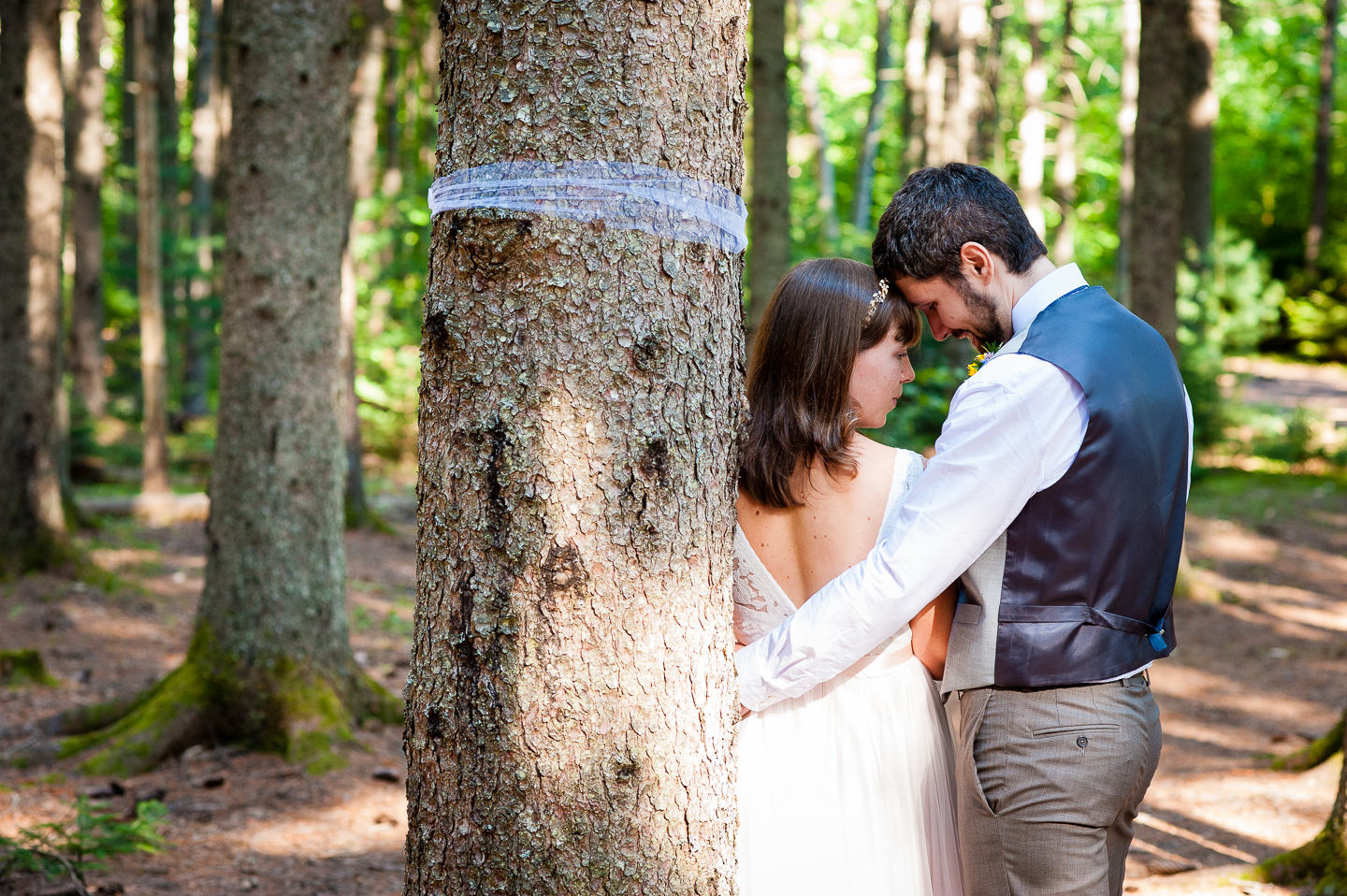 Bride and Groom embrace during their couples portraits in the forest