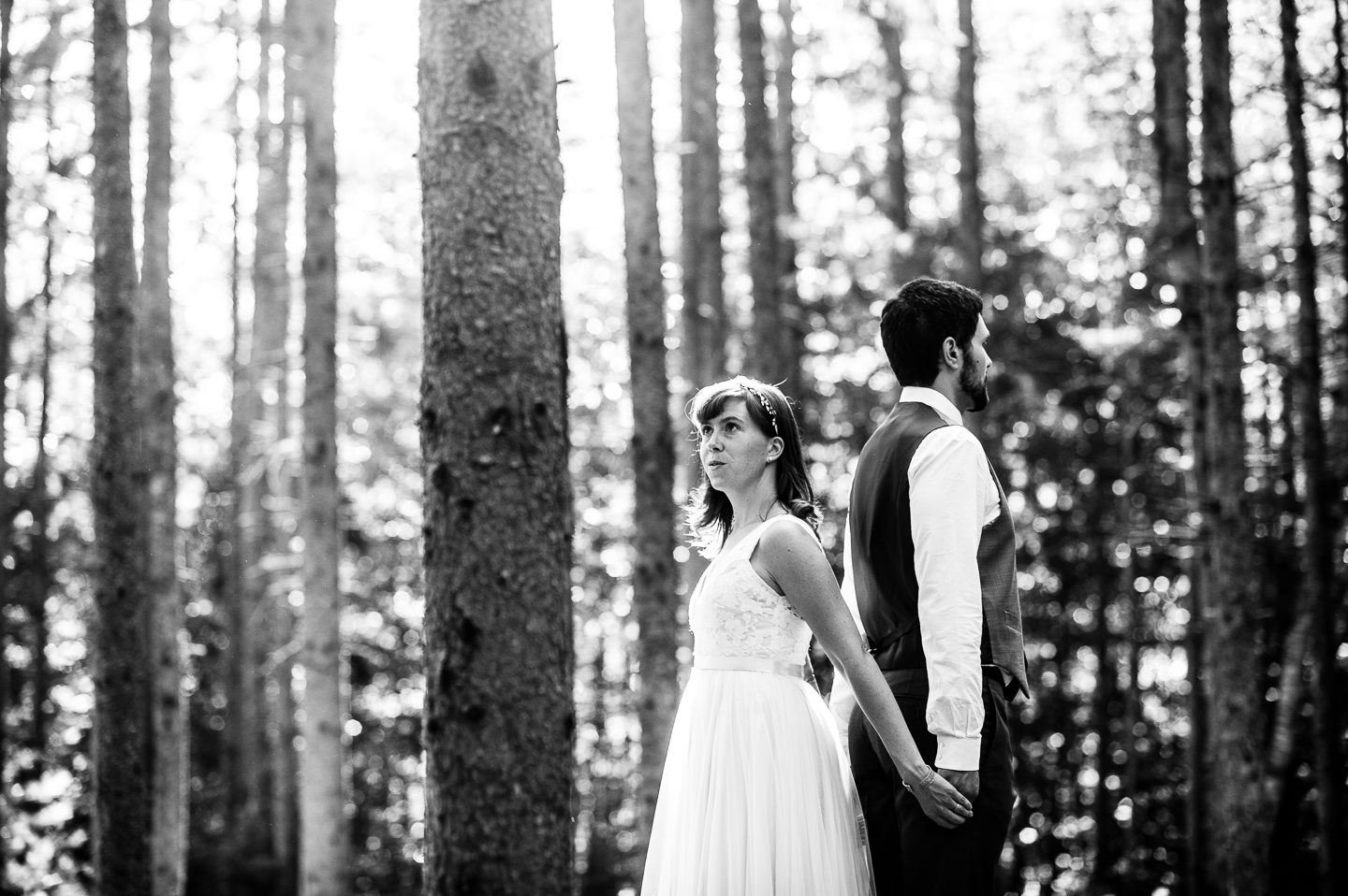 Bride and groom stands back to back holding hands in the middle of the woods