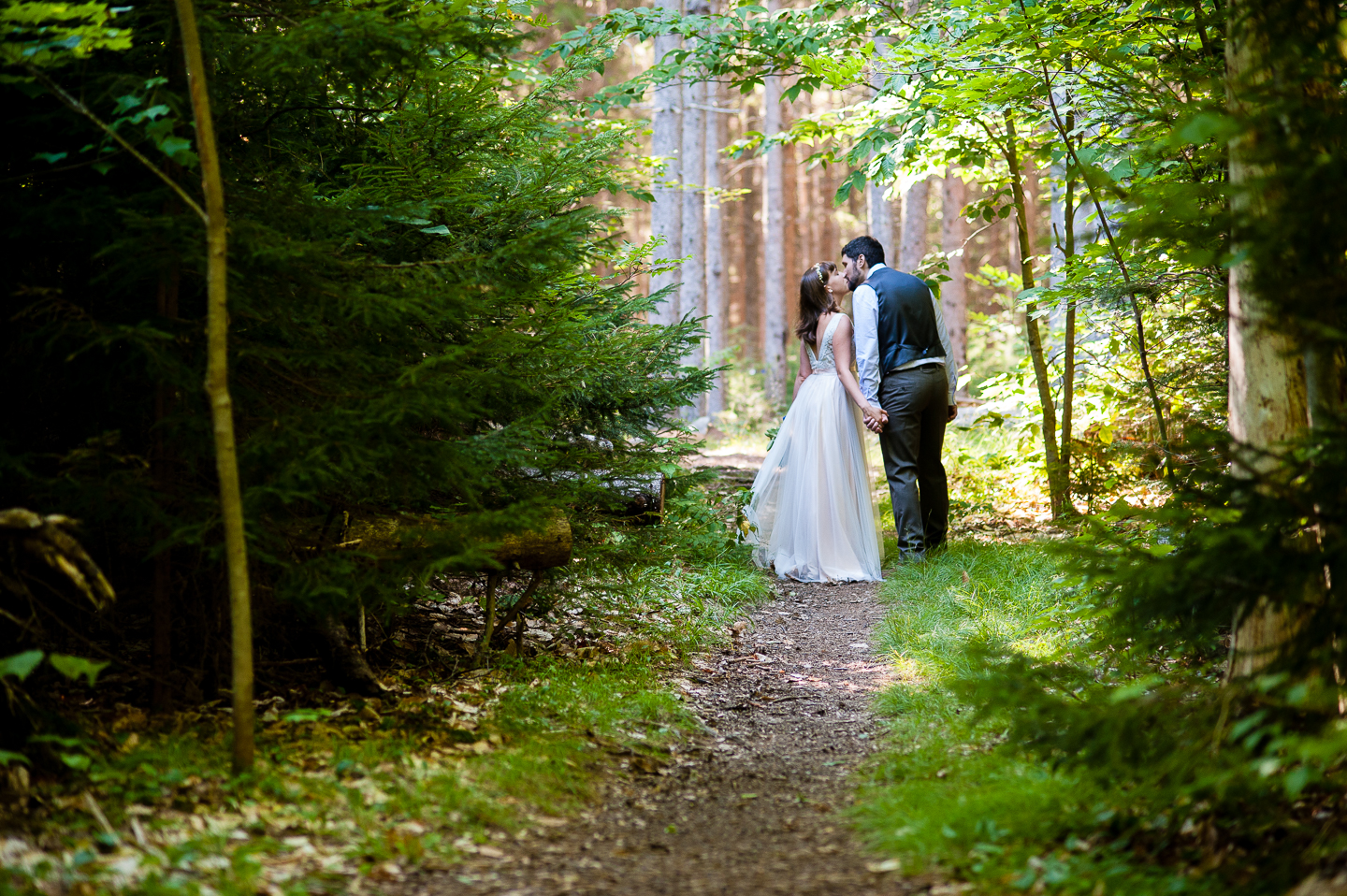 Couple kissing on a gorgeous wooded path