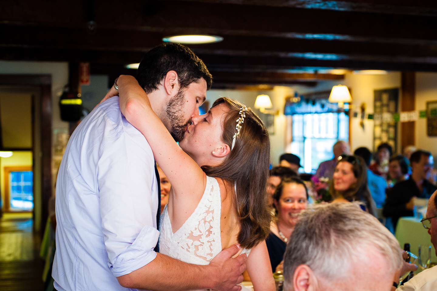 bride and groom kiss at the request of guests during their lodge style mountain wedding reception