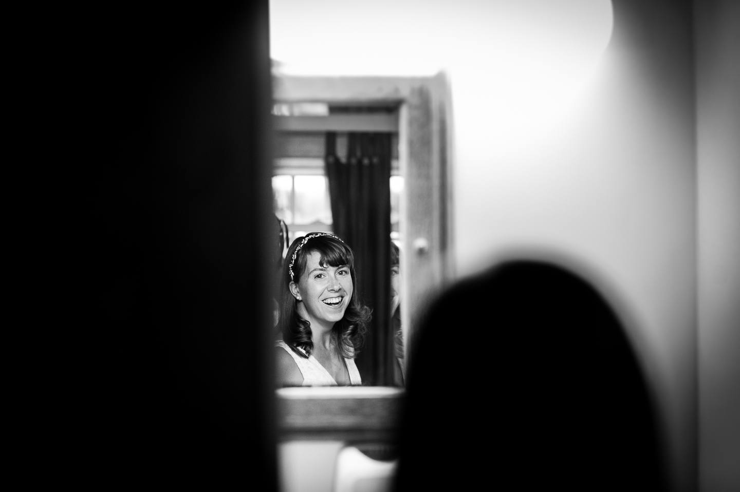 beautiful bride smiling into the mirror just before she heads to her woodsy wedding ceremony