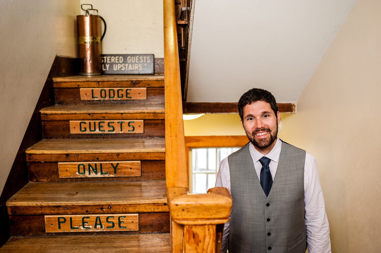 handsome groom stands on AMC Cardigan Mountain lodges staircase