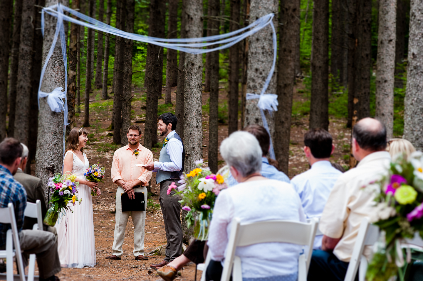 The bride and groom saying their vows during their gorgeous ceremony in the middle of the woods