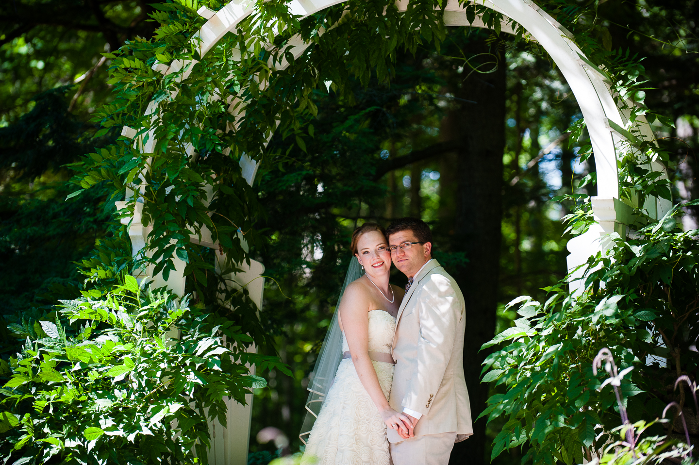 beautiful bride and groom put their heads together for a quick portrait under a beautiful garden trellis