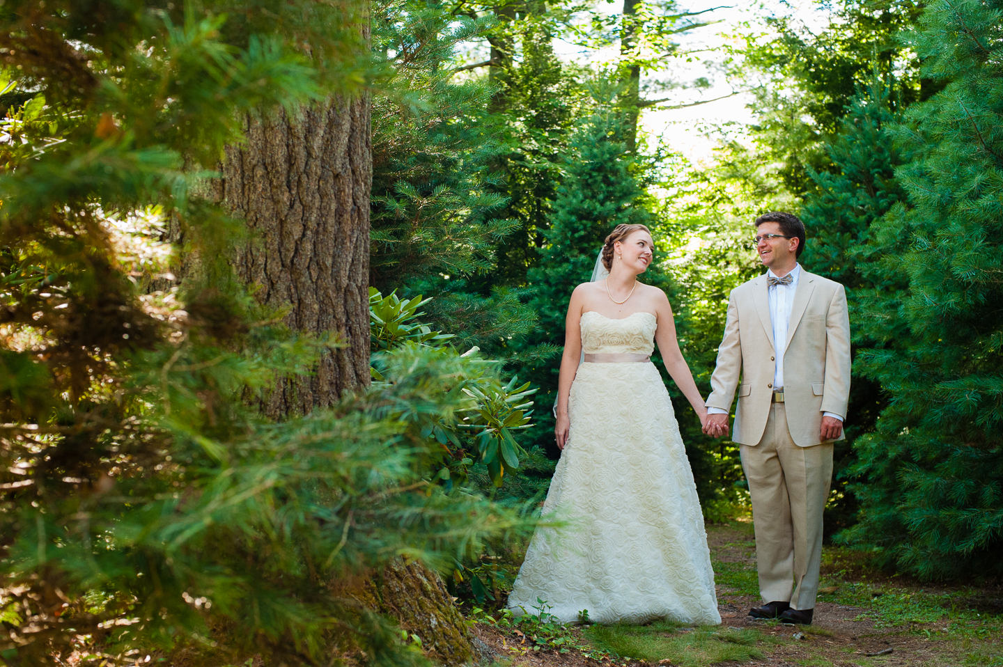 beautiful bride and groom hold hands and walk down a wooded path