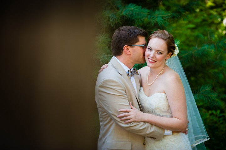 groom gives his gorgeous bride a kiss on the cheek during their beautiful garden wedding