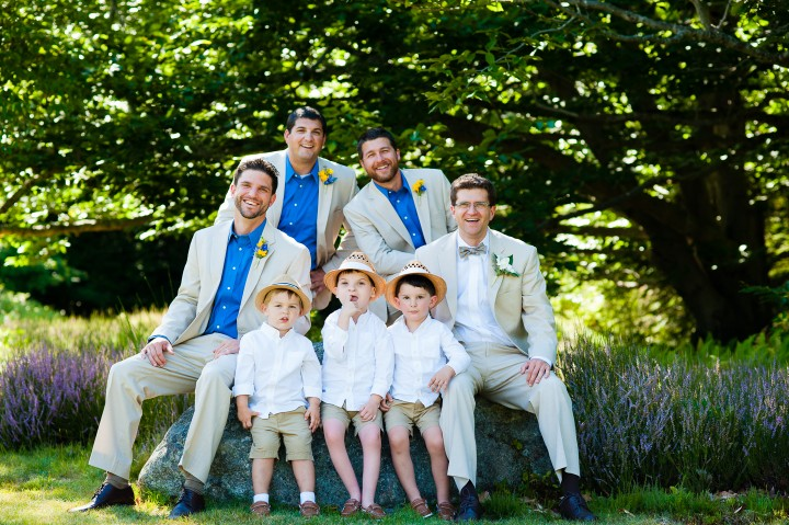 the groom and all his guys sit with the little ring bearers on a rock in the shade