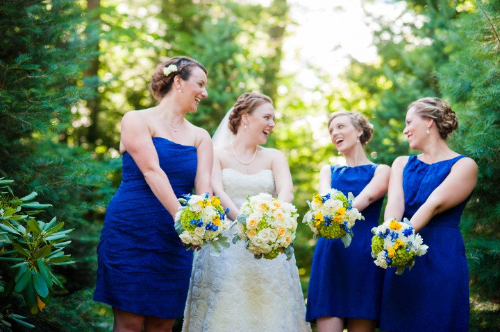 the bride and her beautiful bridesmaids show off their gorgeous bouquets and giggle at each other