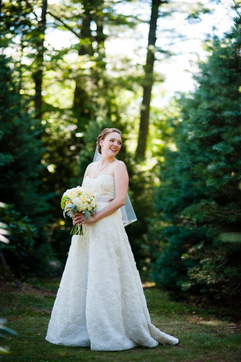 gorgeous bride laughs over her shoulder during her bridal portraits in the woods