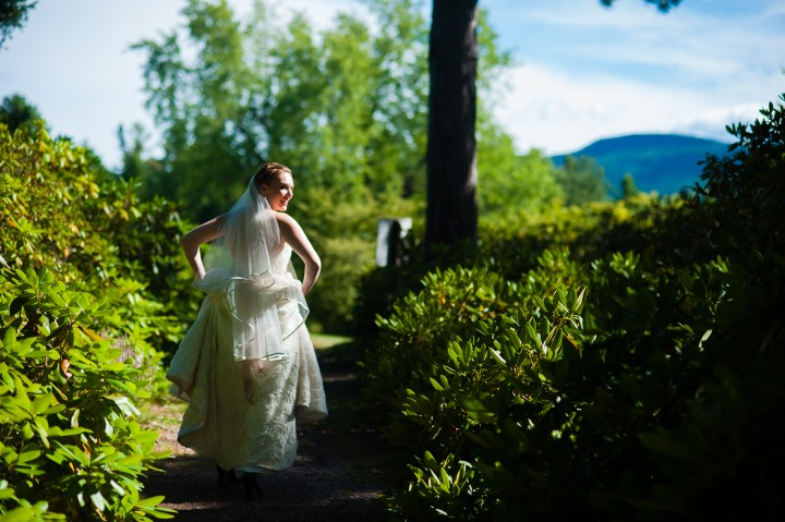 gorgeous bride walks down wooded path with beautiful dappled light