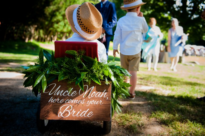 adorable little ring bearers pull a red wagon down the aisle with a cute sign