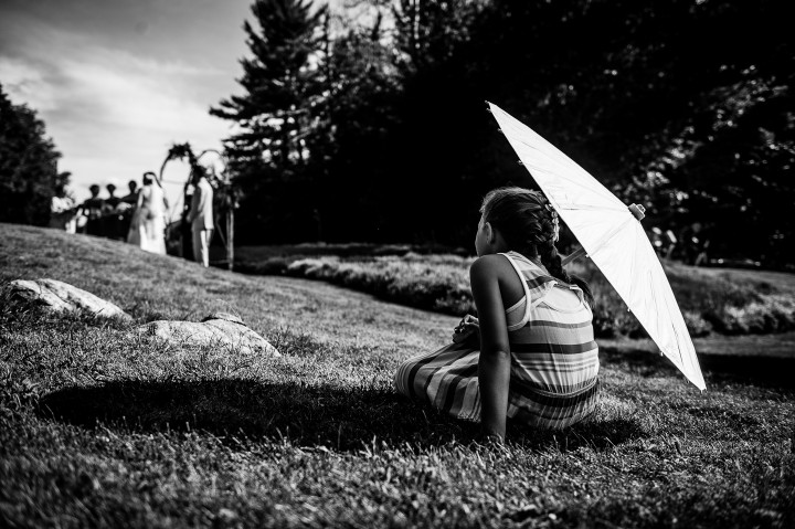 adorable young wedding guest sits in the grass with a sun parasol watching the wedding ceremony