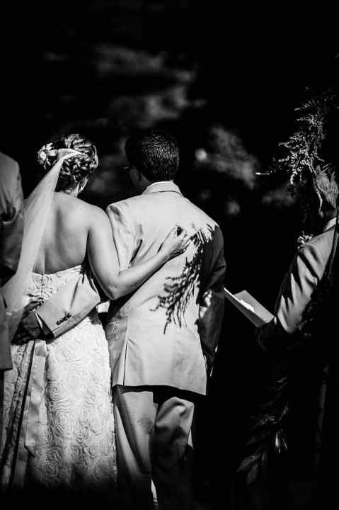love this black and white image of the couple with arms around each other as they listen to ceremony readings