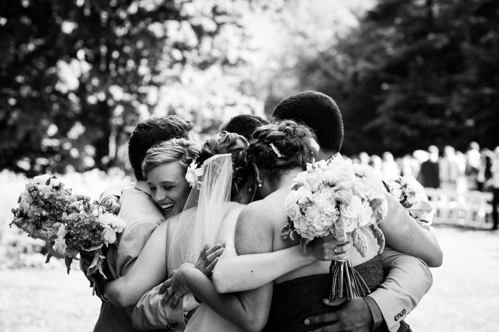 bride and groom and close friends give each other a congratulatory group hug