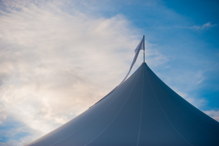 gorgeous sail clothe tent is silhouetted by a bright blue sky