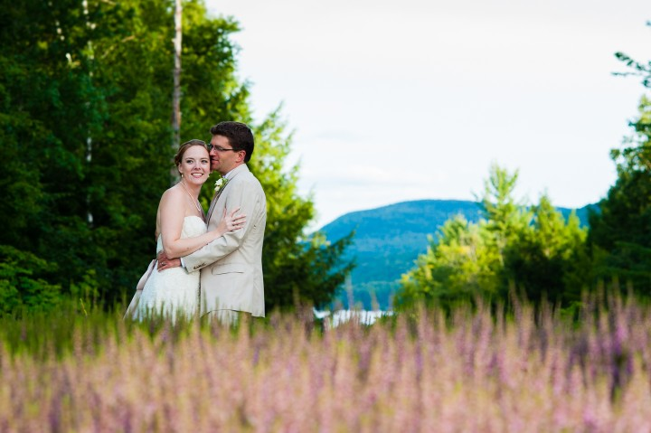 groom gives his beautiful bride a kiss on the check with lake sunapee in the background