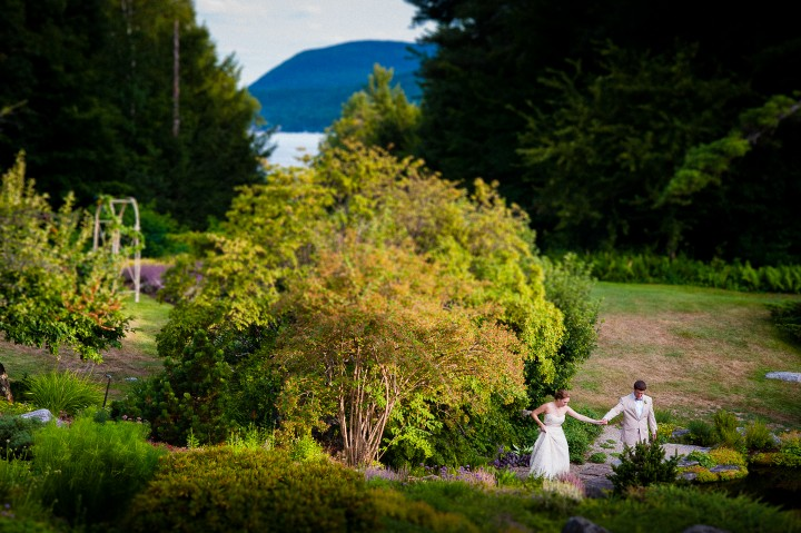 bride and groom hold hands and walk through gorgeous italian garden