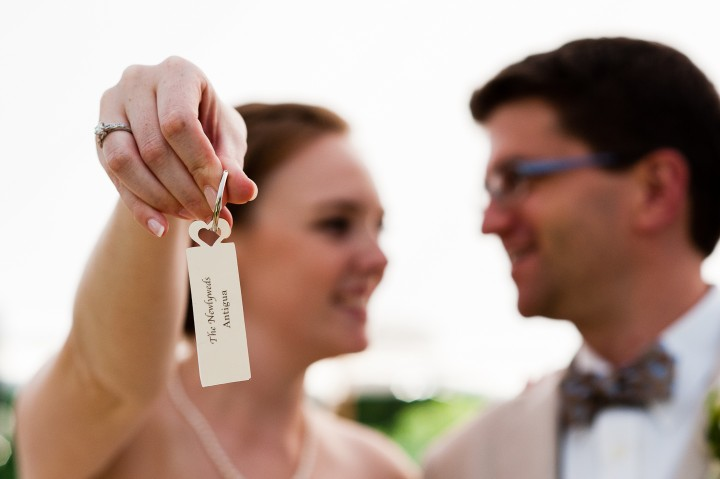 bride and groom hold up their sail cloth tent reception seating tag