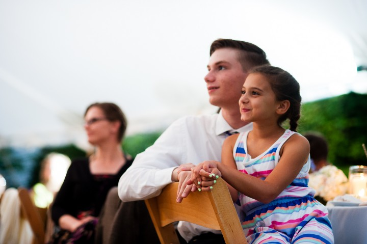two young wedding guests smile at the touching speeches during this wedding reception