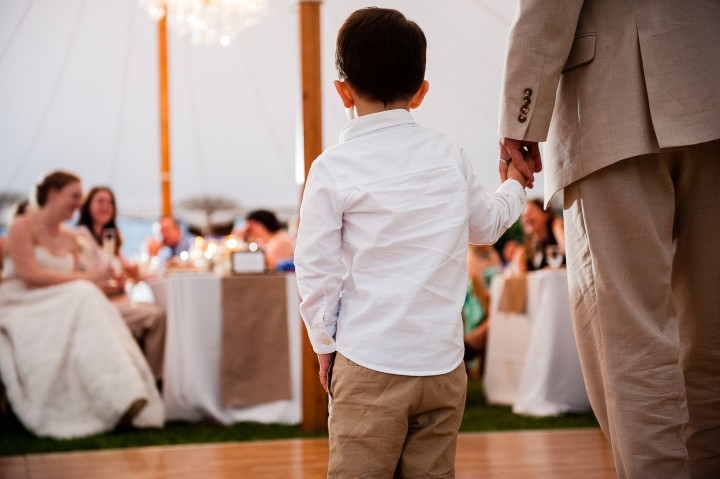 little boy holds his dads hand while his dad gives a wedding toast