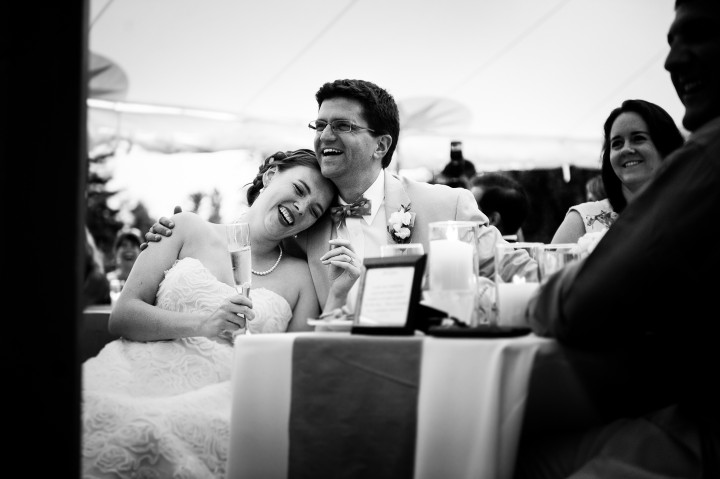 bride and groom cuddle up and laugh during speeches
