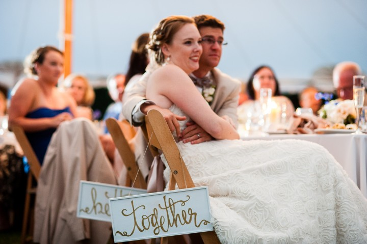 better together signs hung from bride and grooms chair as they listen to speeches