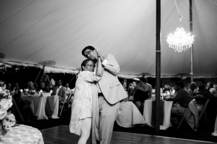 groom and his mom dance during a summer tented wedding