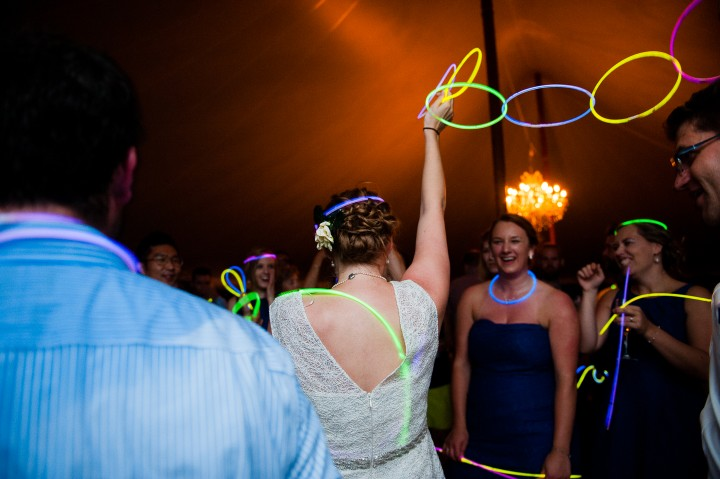 bride swings a chain of glow sticks in the air during her tented wedding reception