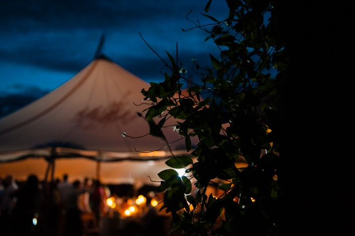 beautiful sailcloth tent lights up at night with bright blue sky behind