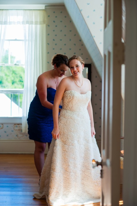 pretty bride poses while her maid of honor zips the back of her gorgeous lace wedding dress