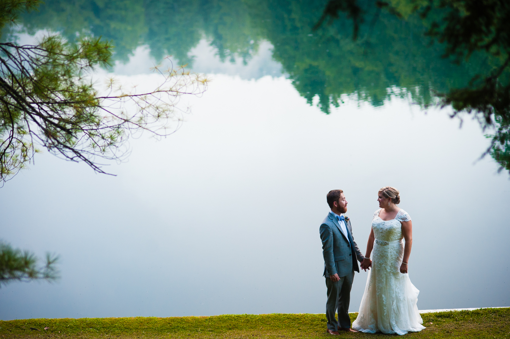 Bride and Groom hold hands with a beautiful misty lake behind during their mountain summer camp wedding