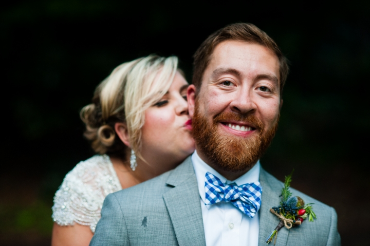 Beautiful bride gives her groom a kiss on the cheek during their wedding a beautiful summer camp wedding