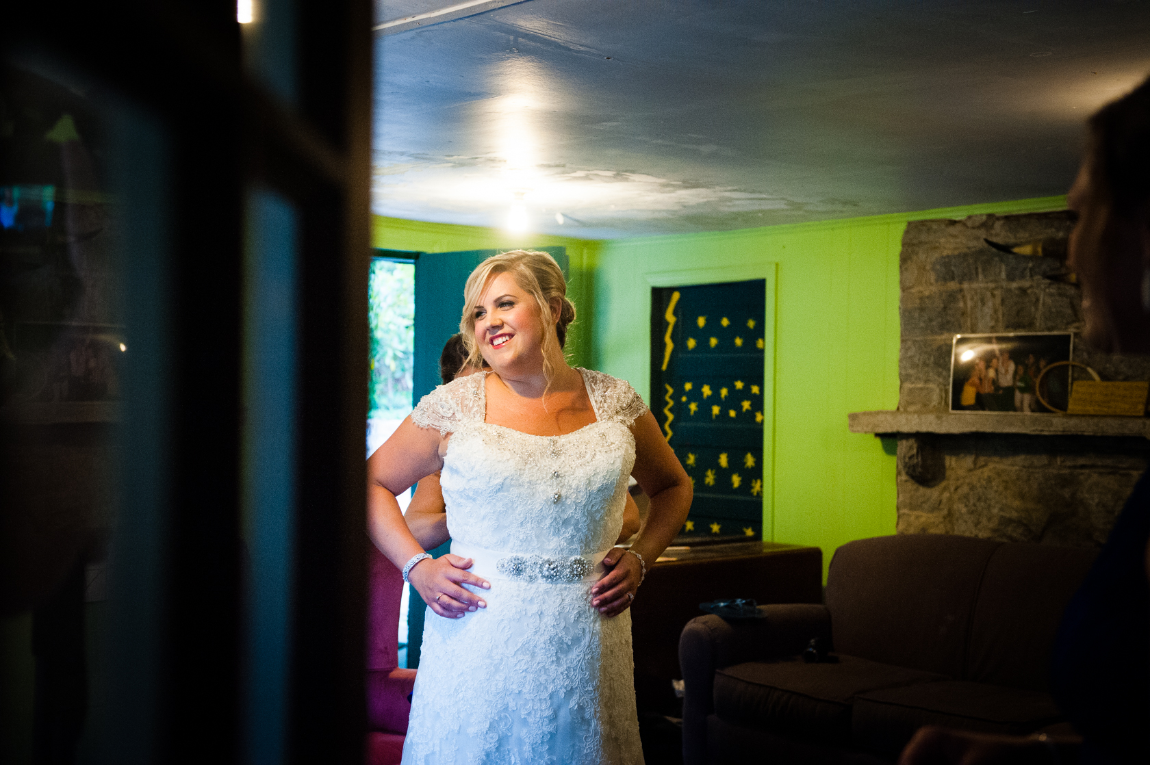 Gorgeous brides gets into her lace dress in the bunk house of a summer camp cabin