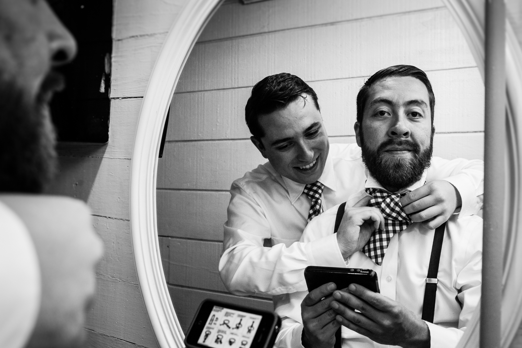 reflection of groom and his best man helping him tie his tie