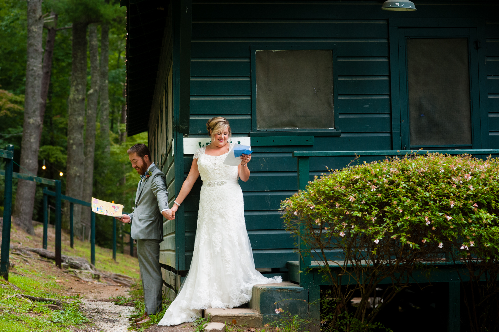 bride and groom hold hands around the corner of a mountain cabin