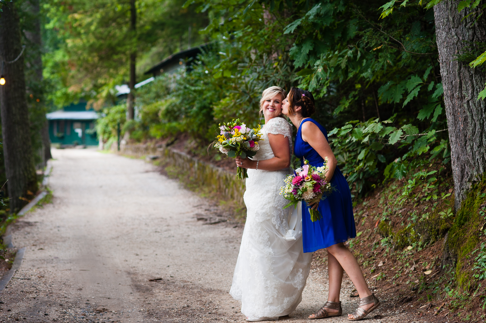 bridesmaid gives beautiful bride a kiss on the cheek on a winding forest lane