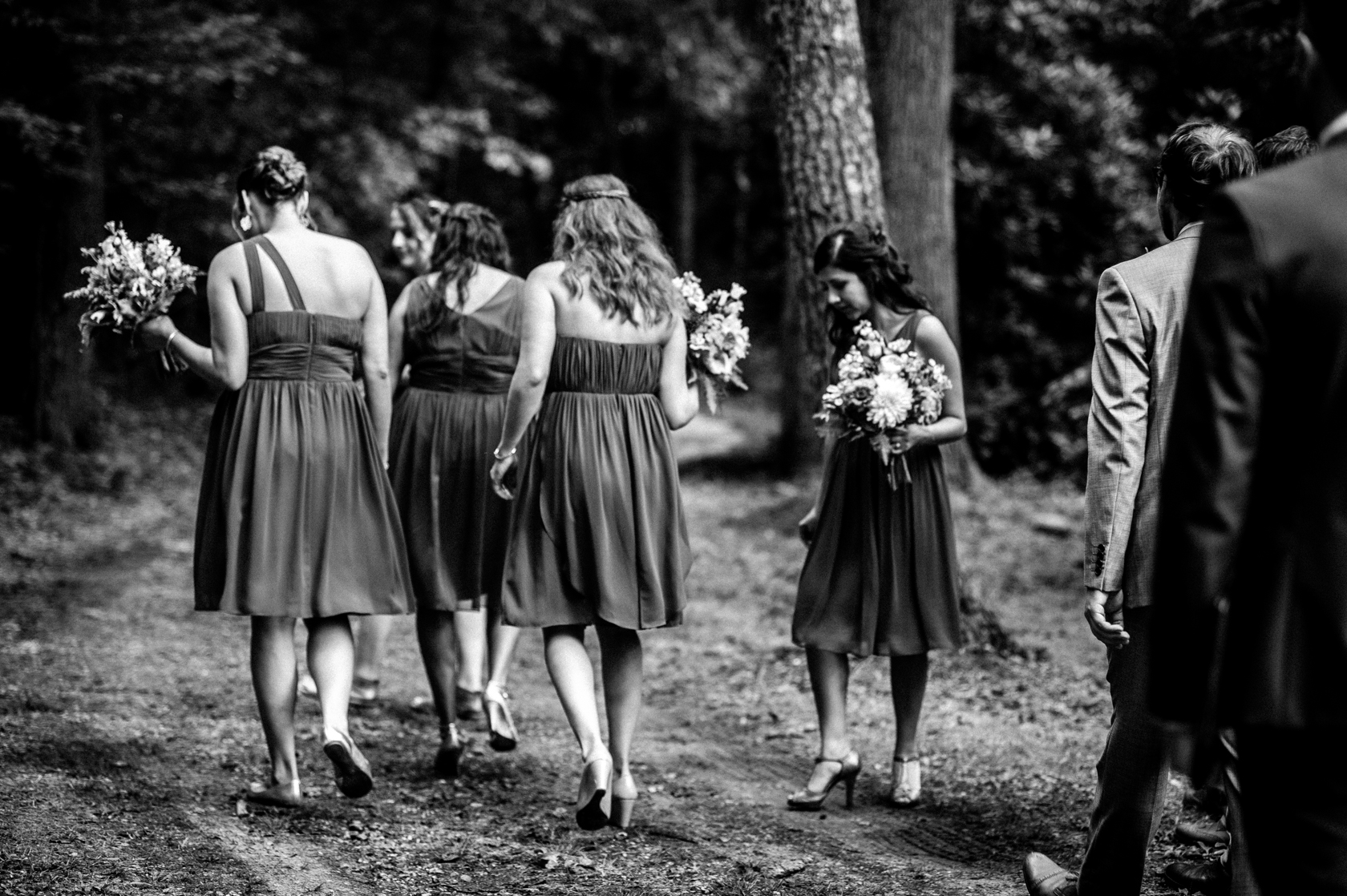 the beautiful bridesmaids wander down a forest path to the ceremony of a summer camp wedding