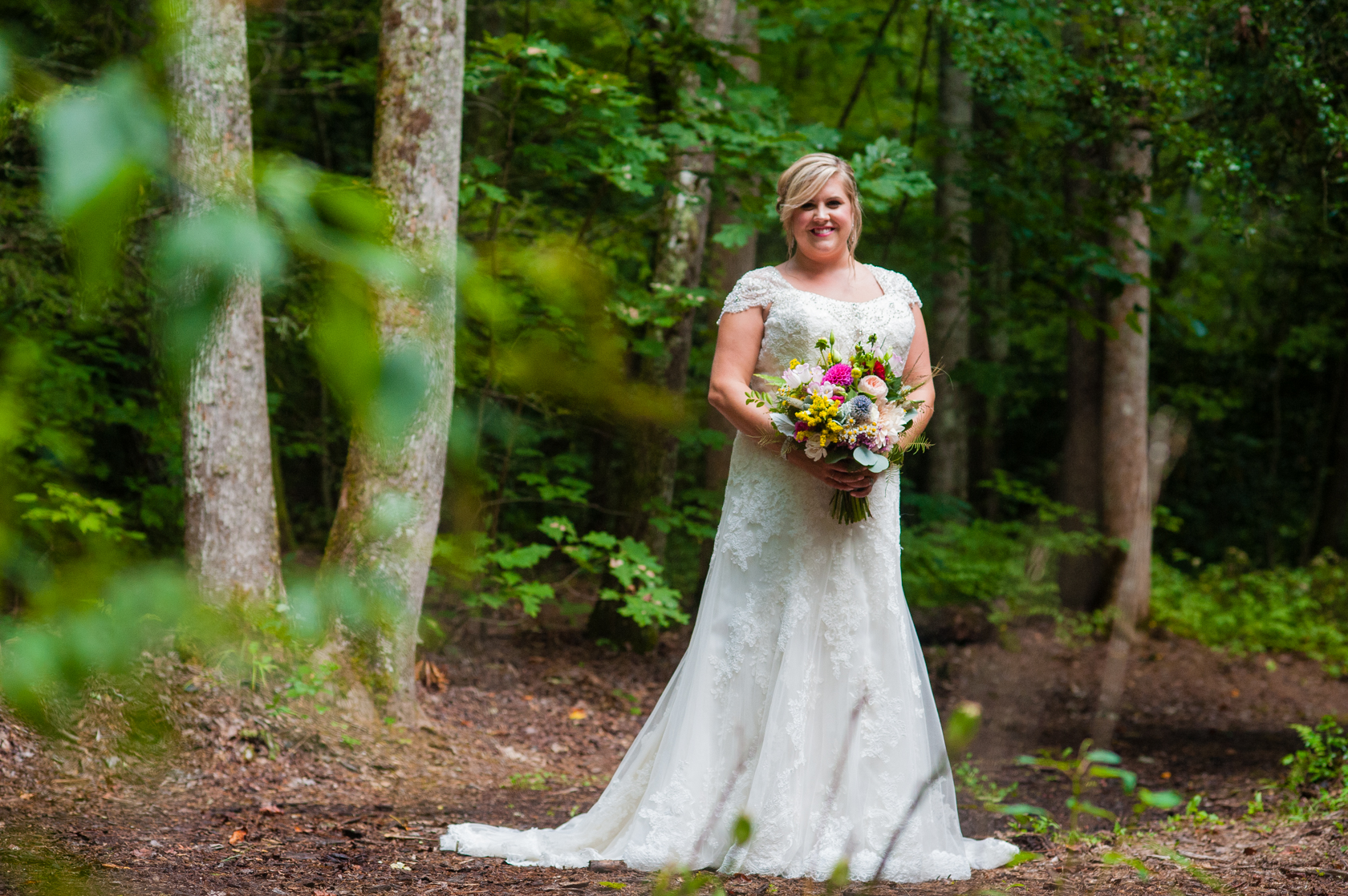 gorgeous bride holds her colorful bouquet on a wooded path