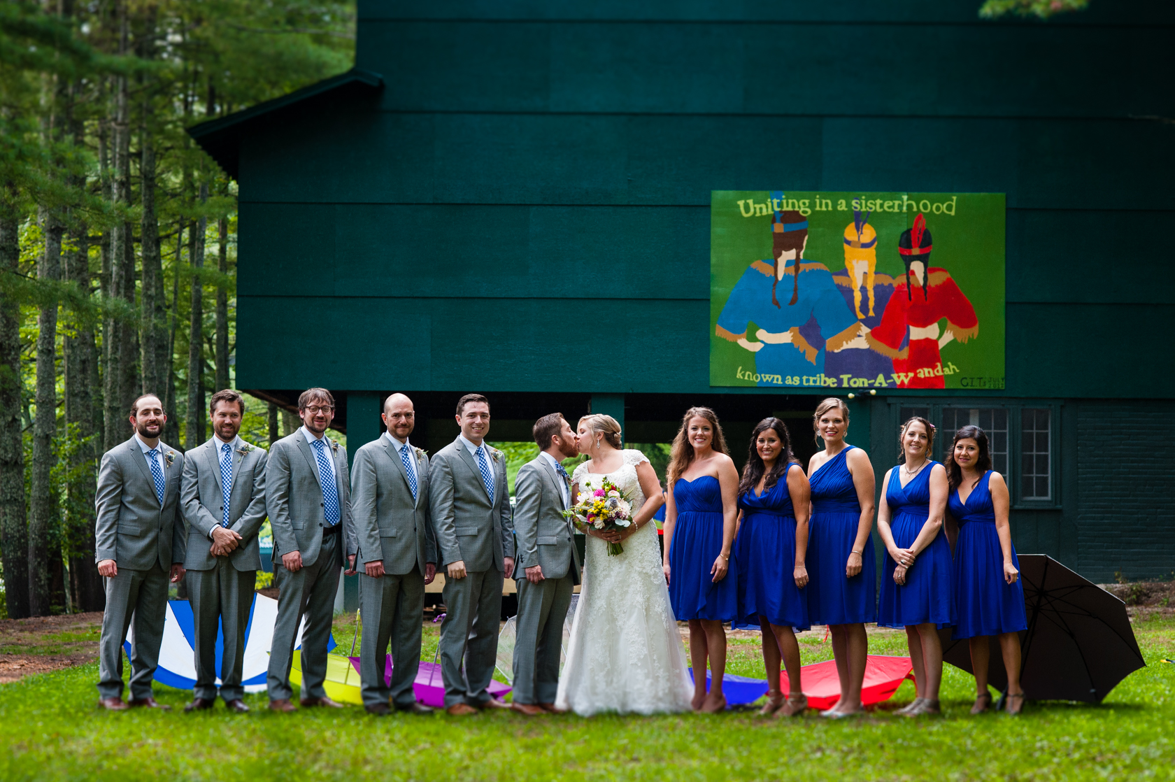 bride and groom with their wedding party stand together in front of Camp Ton a Wandah's bunk house