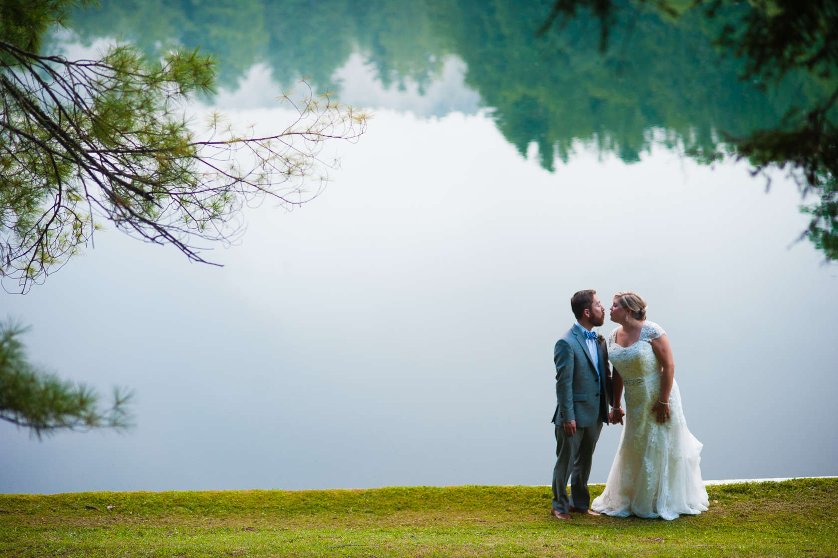 beautiful bride and groom kiss in front of a mountain lake with tree reflections