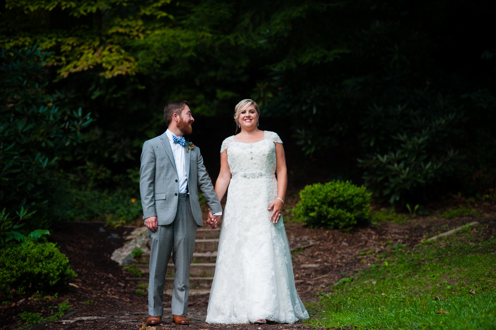 husband looks at his beautiful bride during couples portraits in the woods