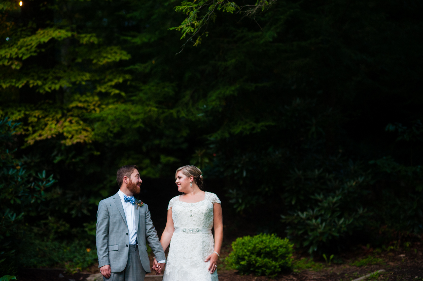 bride and groom hold hands during their portraits in the woods