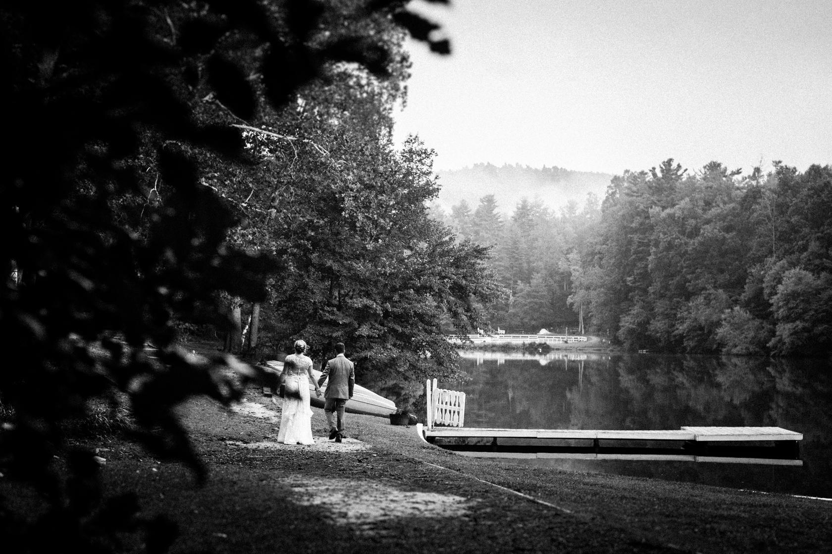 bride and groom walk hand in alongside a misty mountain lake