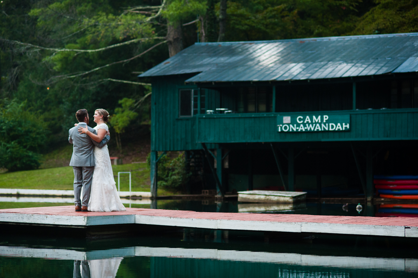 husband and wife practice their first dance on the boat dock at camp ton a wandah
