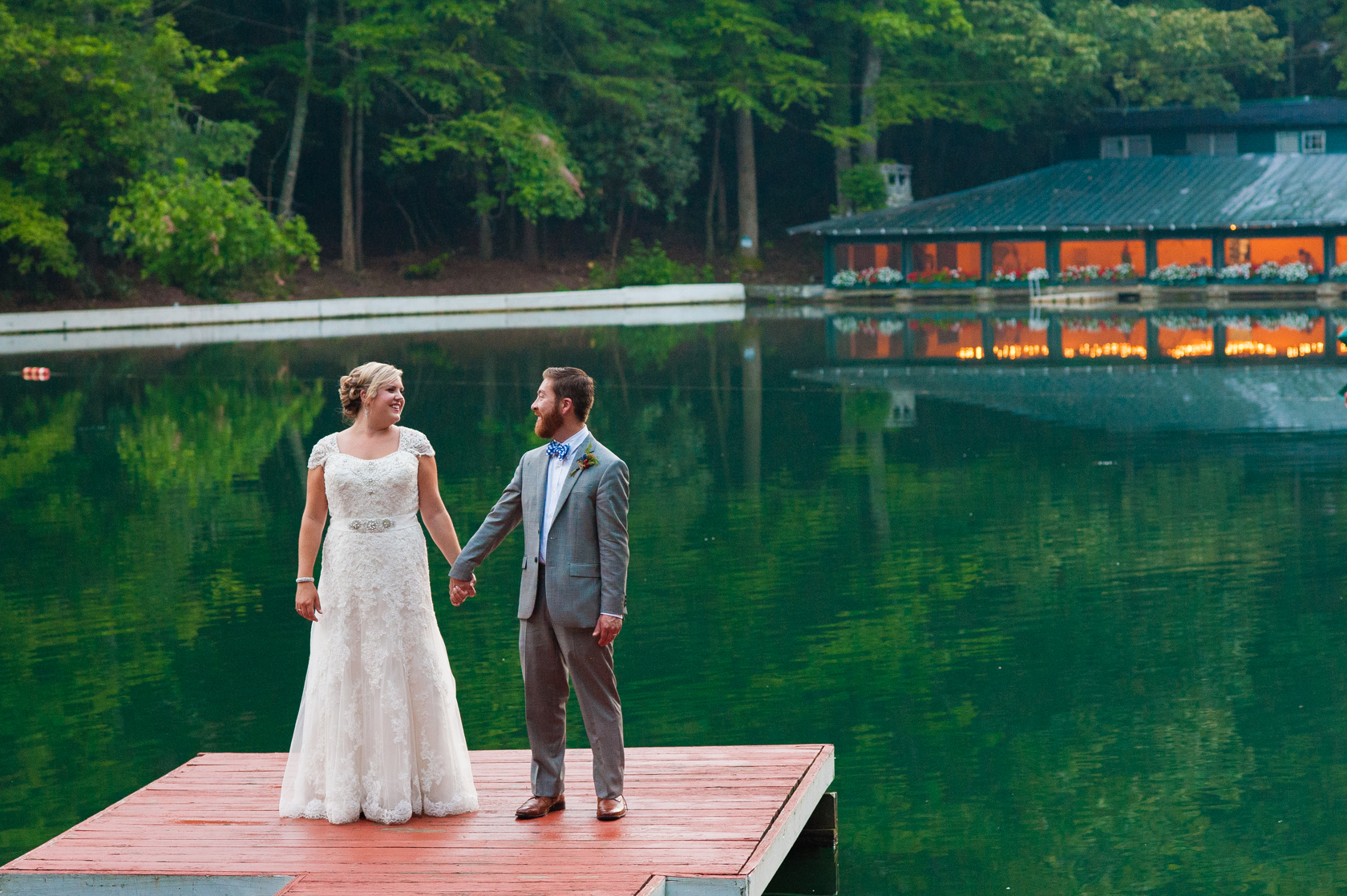 newly married couple holding hands during their summer camp wedding portraits