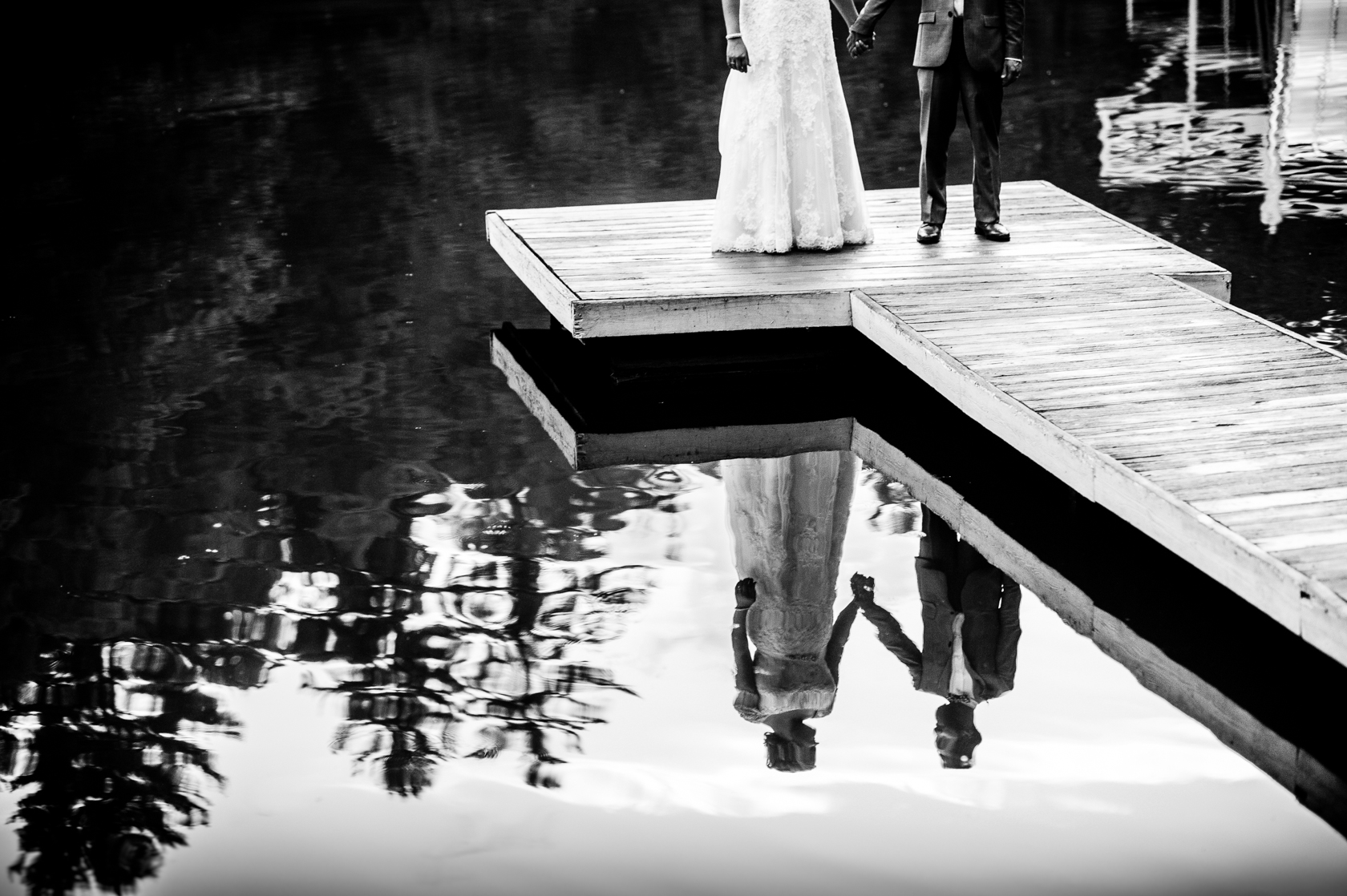 black and white reflection of bride and groom holding hands in mountain lake